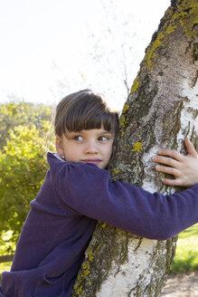 Portrait of girl hugging birch tree - LVF002148