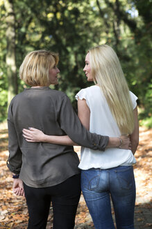 Mother and adult daughter embracing in park - GDF000514