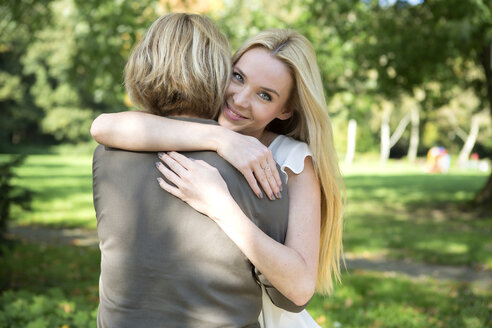 Mother and adult daughter embracing in park - GDF000532