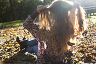 Teenage girl with autumn leaves in her hair sitting in backlight - SARF000958