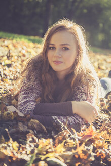 Portrait of teenage girl lying on the ground covered with autumn foliage - SARF000957