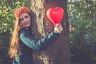 Portrait of smiling teenage girl with heart shaped balloon hugging a tree - SARF000970