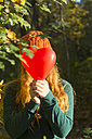 Teenage girl hiding her face behind heart shaped balloon - SARF000951