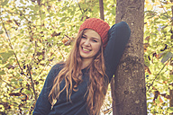 Portrait of laughing teenage girl leaning at tree in autumn - SARF000950