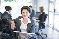 Smiling businesswoman with meeting in the background - ZEF002227