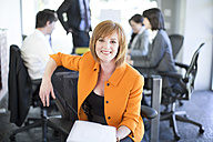 Smiling businesswoman with meeting in the background - ZEF002155