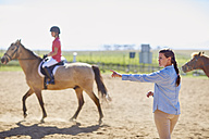 Coach and girl on horse on riding ring - ZEF001709