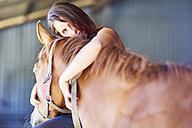 Teenage girl embracing horse in stable - ZEF001741