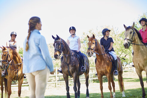 Coach and girls on horses on riding ring - ZEF001746