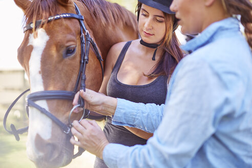 Woman and teenage girl with riding horse - ZEF001749