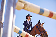Young woman on horse approaching obstacle on course - ZEF001763
