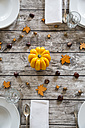 Autumnal laid table with yellow pumpkin, chestnuts and acorns - LVF002093