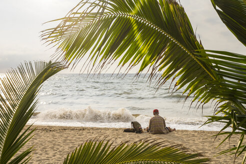 Mexico, Jalisco, Puerto Vallarta, A homeless man is sitting next to his backpack at a beach - ABA001545