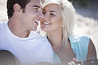 Young man playing guitar with his girlfriend on the beach - ZEF002443