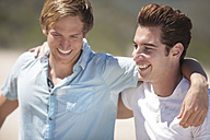 Two friends arm in arm on the beach - ZEF002464