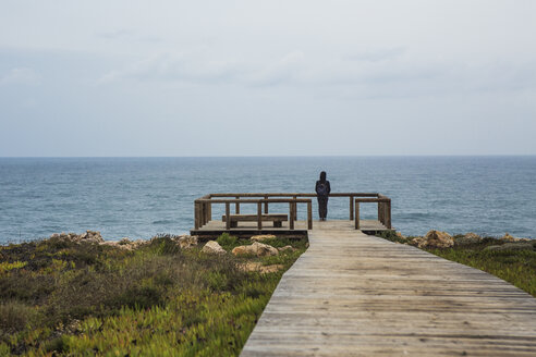 Portugal, Algarve, Carrapateira, person standing on wooden view terrace looking at the sea - KBF000212