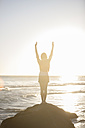 Young woman standing on rock on the beach at sunset - ZEF002483