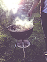 Germany, Man with kettle barbecue in garden - LVF002108
