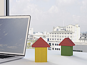 Building blocks formed like houses and laptop on desk in front of a window - UWF000211