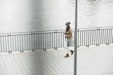 Young woman walking at promenade orientating with digital tablet - UUF002357