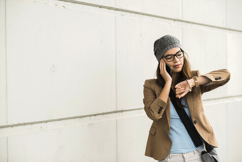 Young woman telephoning with smartphone while checking time - UUF002463