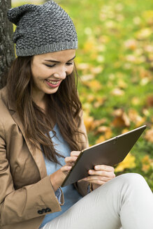 Smiling young woman leaning against a tree using digital tablet - UUF002382