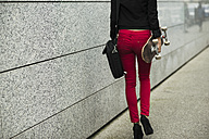Young woman with bag and skateboard wearing red trousers, partial view - UUF002407