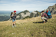 Austria, Tyrol, Tannheimer Tal, young man taking picture of girlfriend on alpine meadow - UUF002451