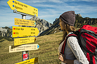 Austria, Tyrol, Tannheimer Tal, young woman on hiking trip at signpost - UUF002462