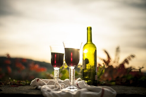 Bottle of red wine and two glasses in evening sun - SBDF001411