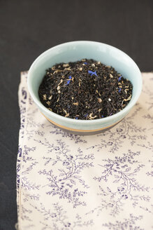 Bowl of Earl Grey blend mixed with cornflowers on patterned cloth - MYF000666