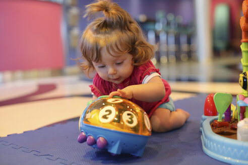 Baby girl playing with toys in a playroom of cruise liner - SHKF000079