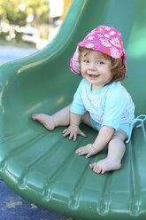 Smiling baby girl on green shute - SHKF000067