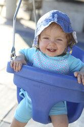 Portrait of smiling baby girl sitting on blue baby swing - SHKF000070