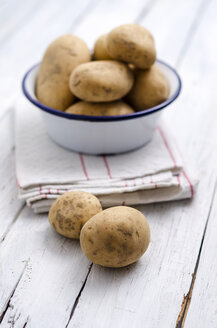 Bowl of raw potatoes on folded kitchen towel and wood - ODF000843