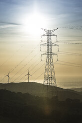 Spain, Andalusia, Tarifa, Wind farm and power pylons in the evening light - KBF000244