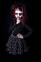Girl with finger on mouth masquerade as devil in front of black background - YFF000254