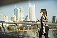 Germany, Frankfurt, young businesswoman on bridge - UUF002468