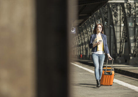 Young woman with cell phone and baggage at train station - UUF002504