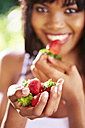 Hand of smiling woman holding strawberries - ZEF001921