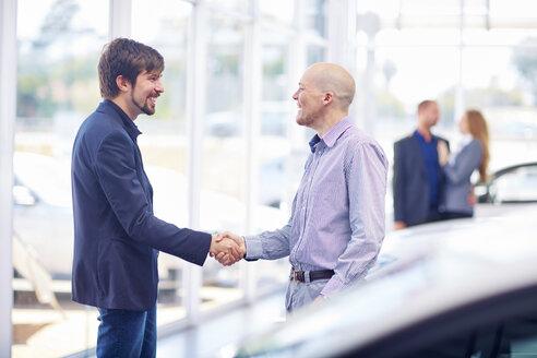 Car dealer and client shaking hands - ZEF002020