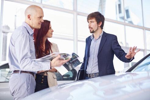 Car dealer with couple in showroom - ZEF002021