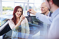 Car dealer giving key to client - ZEF002025