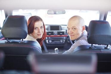Smiling couple at car dealer inside car - ZEF002035