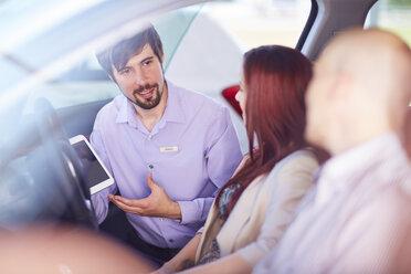 Car dealer talking to couple inside car - ZEF002038