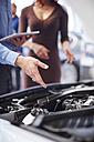 Car dealer explaining car engine - ZEF002053