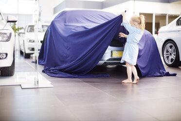 Girl at car dealer unveiling tarpaulin - ZEF002136