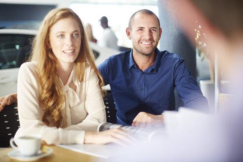 Smiling couple at car dealer - ZEF002138