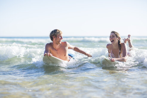 Happy young couple lying on surfboards in the sea - ZEF002399