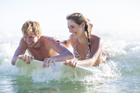 Happy young couple lying on surfboards in the sea - ZEF002402